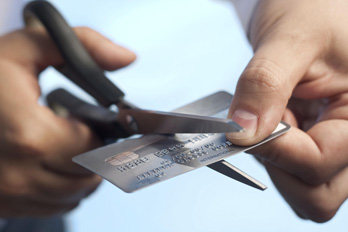 Scissors cutting a credit card to eliminate debt